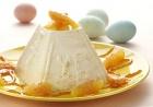 Пасха из рикотты с апельсином::Что нужно: сыр Рикотта - 400 г; апельсин - 2 шт.; масло сливочное - 50 г; сахар - 1 стакан; сливки жирностью 20% - 100 мл; пудра сахарная. Как готовить: У апельсина срезать полосками кожуру вместе с внешней пленкой. Вырезать мякоть, находящуюся между внутренними пленками, и сложить ее в миску. В ту же миску отжать сок из остатков апельсина. Повторить со вторым апельсином. В сковороде разогреть сливочное масло, посыпать сахаром. Готовить 5 минут, затем добавить мякоть и сок апельсинов. Готовить, помешивая, до образования жидкой карамельной массы. Влить сливки, перемешать и снять с огня. Дать остыть. Понемногу, непрерывно перемешивая, добавить апельсиново-сливочную смесь в рикотту.Полученную массу уложить в пасочницу (или пасочницы), поместить в холодильник до полного застывания на 1,5 - 2 ч, а лучше на ночь. Подать, посыпав сахарной пудрой через сито.